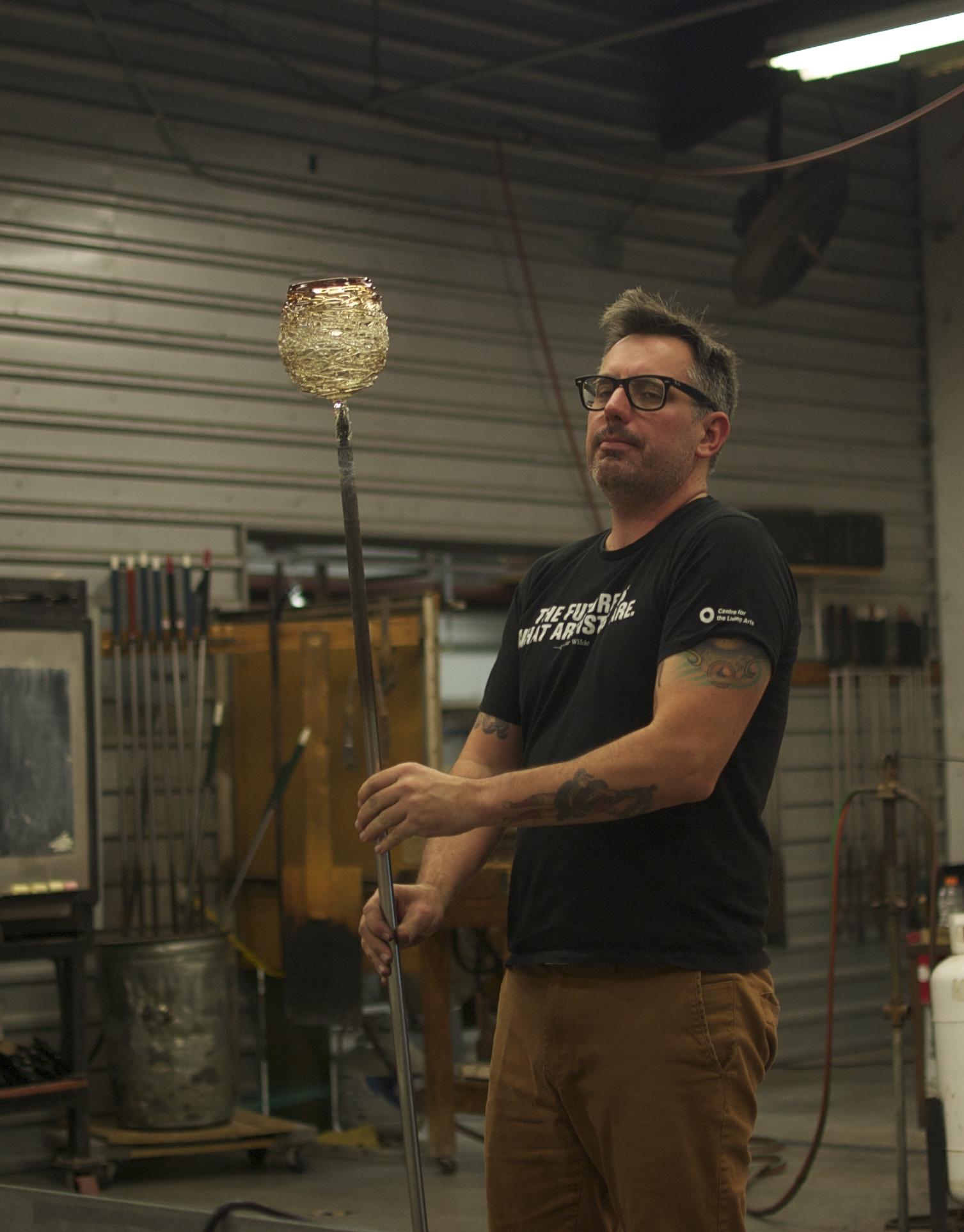 Glass blower showing off a bird's nest light fixture cover