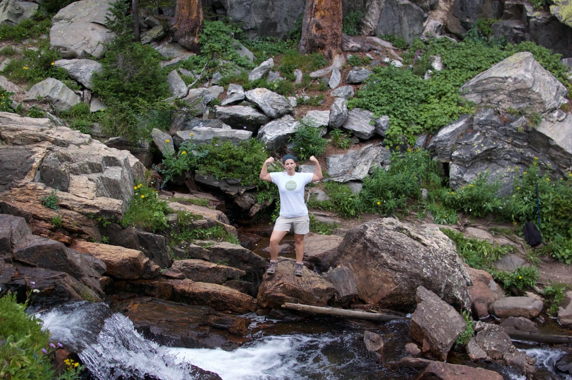 Strong woman near a waterfall