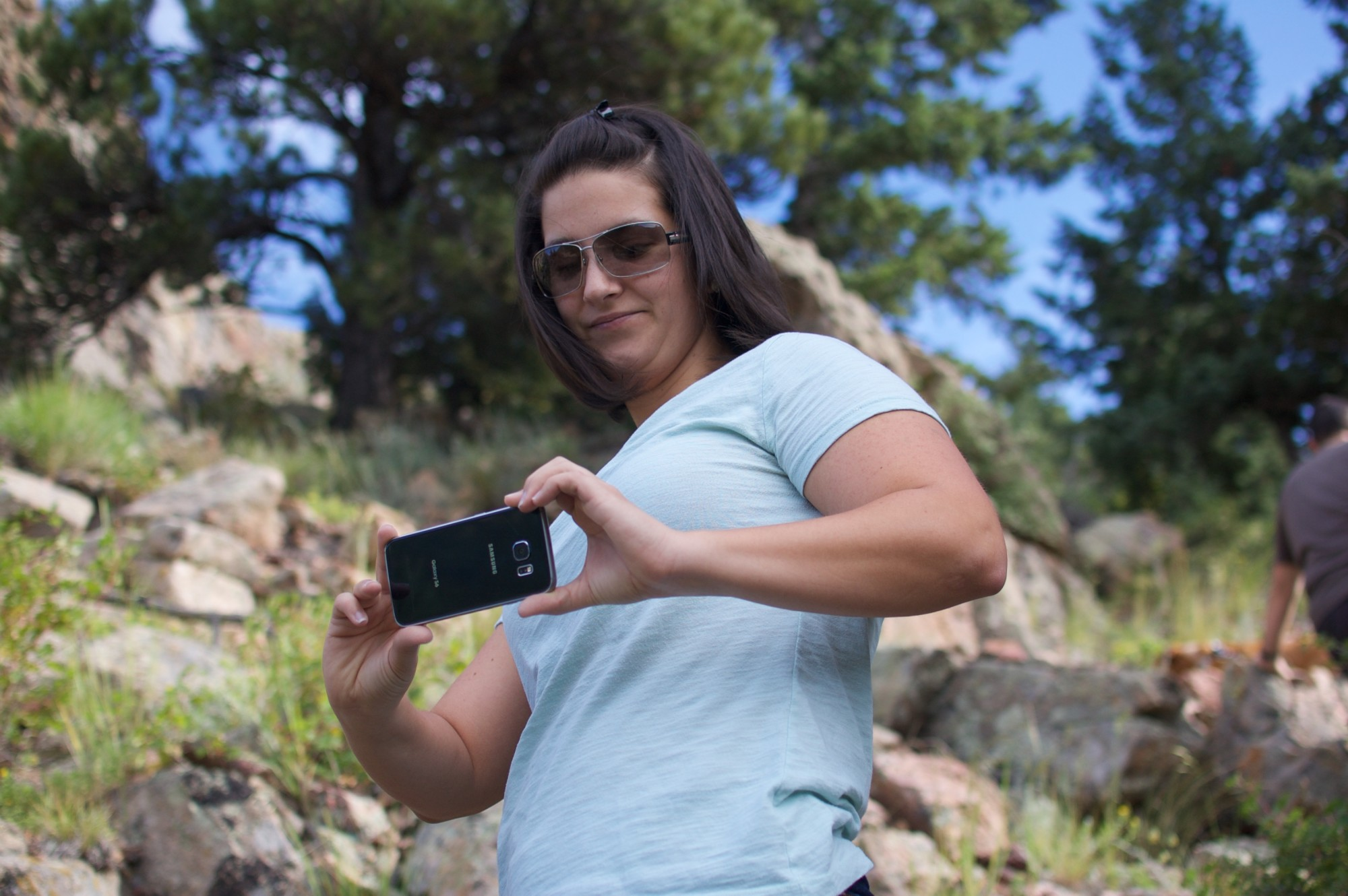Jessy taking a picture with her cell phone on a hike
